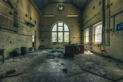 Former psychiatric hospital, regional NSW. Photographer's note: The engineering department workshop that hasn't seen anyone strike a blow for the better part of twenty years. The tiled walls and floor and the grand arch window were pretty fancy for an industrial working area like this.
